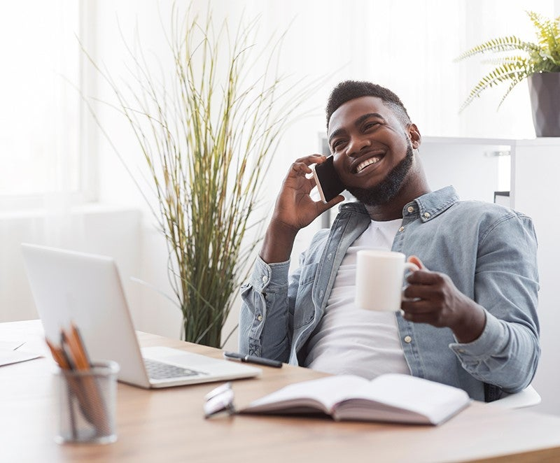 Man on laptop drinking coffee