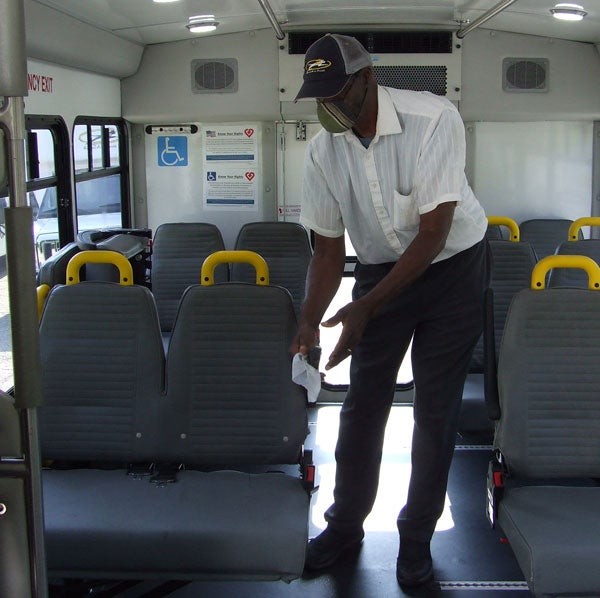 VAC Driver Willie Moore cleaning bus seats, 2020.