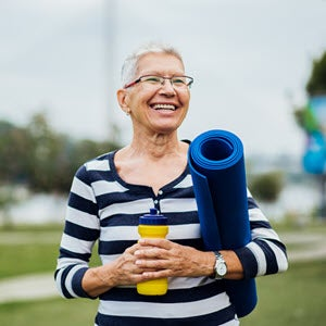 Senior woman with yoga mat and water bottle