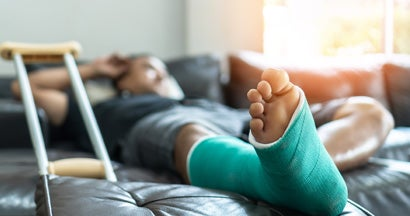 Male patient with splint cast and crutches during surgery rehabilitation and orthopaedic recovery staying at home