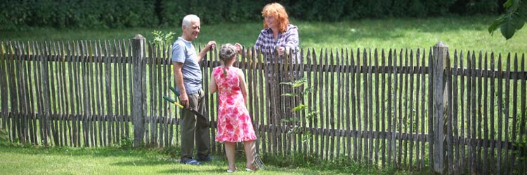 Grandparent and girl with neighbor in garden