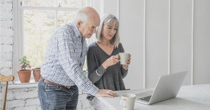 A senior man and his wife are looking at a laptop computer together.