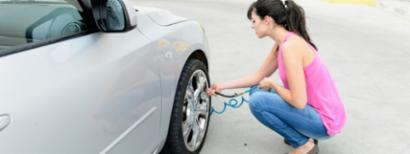 Teen girl checking the tire pressure
