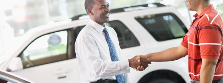Two men shaking hands on a successful negotiation in a used car dealership.