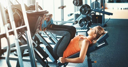 woman doing an incline leg press in then weight room