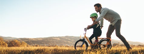 Photo of a young boy and his father learning to ride a bike.