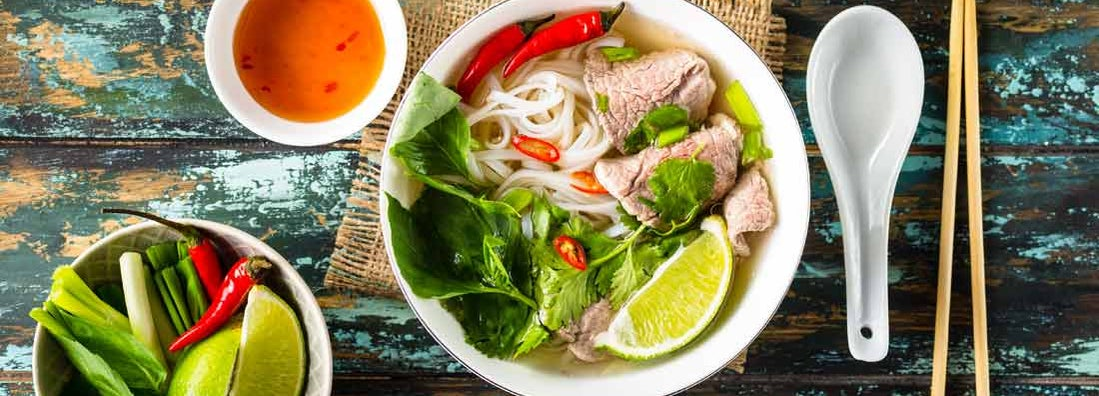 Traditional Vietnamese soup Pho bo with herbs, meat, rice noodles, broth.