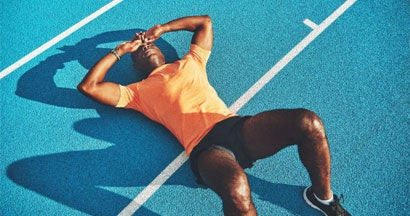 Exhausted young athletic lying on a running track after training
