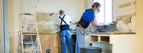 Two men tearing out old kitchen during home renovations
