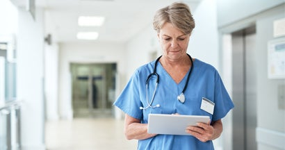 Female nurse using a tablet while standing in the hospital corridor