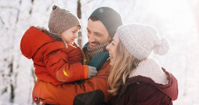 young family, being playful outdoors in nature covered in snow