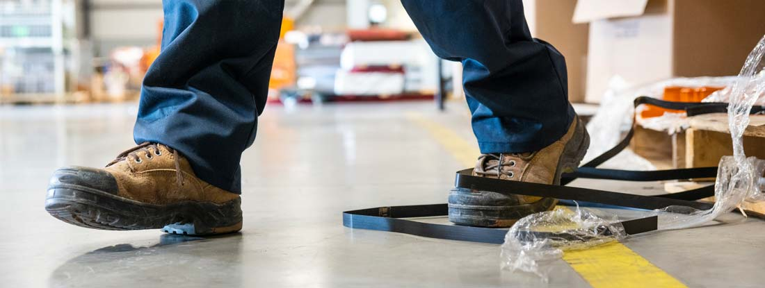 A worker in danger of tripping over a piece of metal strapping in a factory.