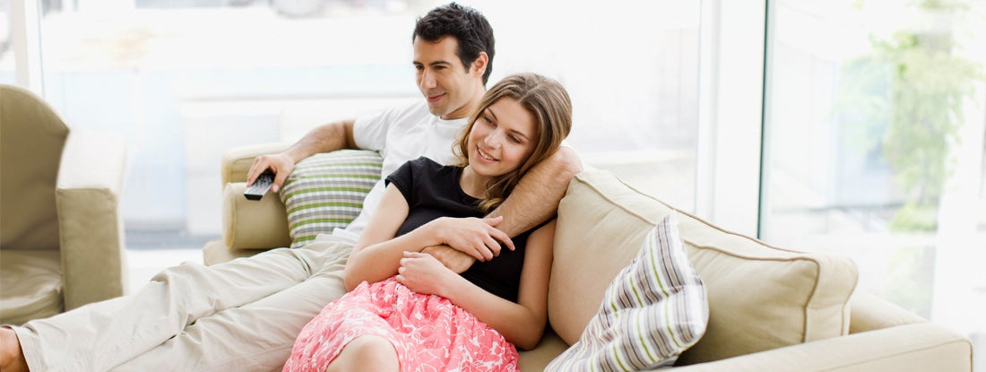 Couple sitting on sofa in condo