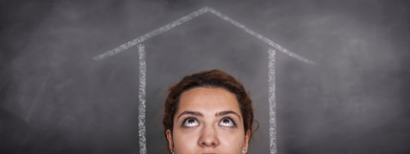 A woman looks up at a drawing of a house on a chalkboard, wondering.