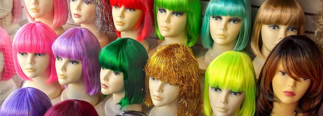 Mannequins Wearing Colorful Wigs in Window of a Wig Shop