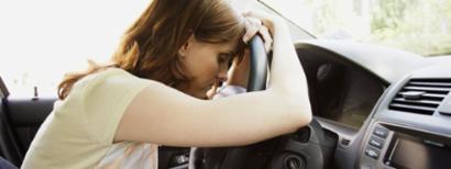 Sad woman in new car.