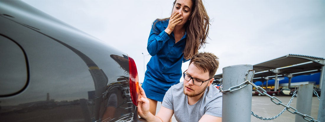 couple examine a dent on their car