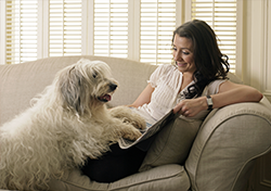 A smiling woman reading with her dog.
