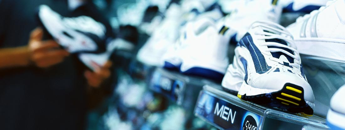 young man looking at shoes in a running shoe store