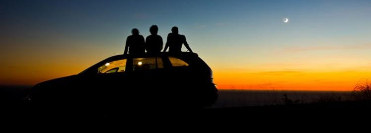 Friends sitting on a new car watching the sunset.
