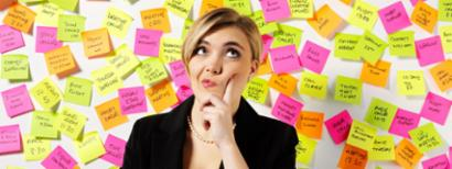 A woman stands in front of a wall of post-it note reminders, wondering.