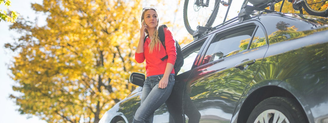 Teen standing next to the car using her smartphone