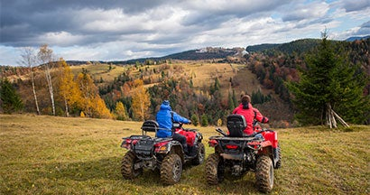 a couple overlooking a landscape on their atv