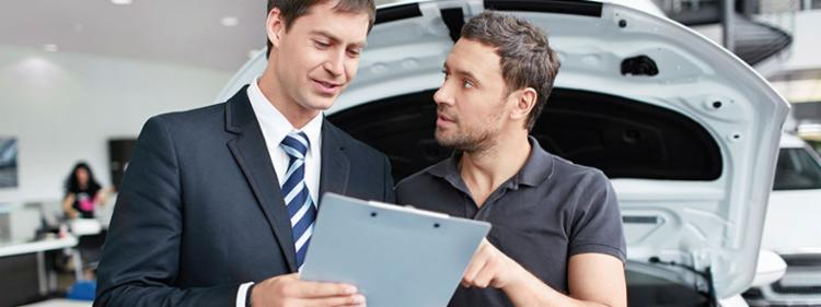 A man questioning his car dealer on some paperwork.