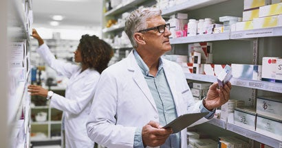 Two pharmacist walking around and doing stock inside of a pharmacy