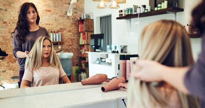 Blonde woman sitting in a chair talking with her hairstylist while having her hair done during a salon appointment