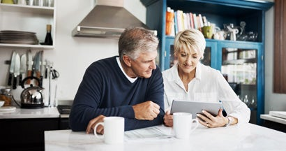Mature couple using digital tablet to search for an annuity specialist