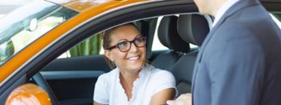 A woman preparing to test drive a new orange car.