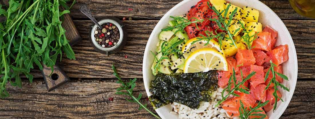 Hawaiian salmon fish poke bowl with rice, avocado, mango, tomato, sesame seeds and seaweed.