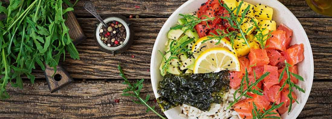 Hawaiian salmon fish poke bowl with rice, avocado, mango, tomato, sesame seeds and seaweed.