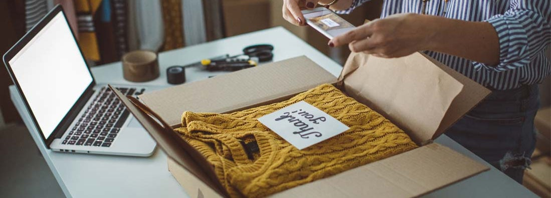 Small business owner packing product in boxes, preparing it for delivery.