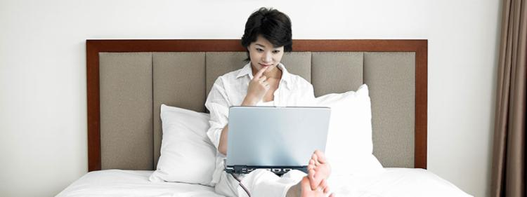 A woman does research on a laptop in her bed in the morning.