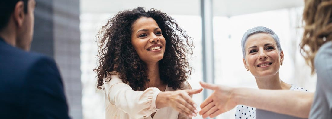 Businesswomen shaking hands with new hire at the office