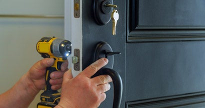 Professional locksmith installing a new deadbolt lock. Ways your home insurance is draining your savings.