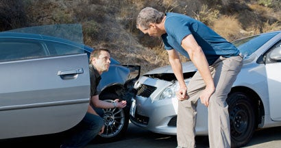 Two men examining damage in car collision. Who's responsible for damages if both drivers were at fault?