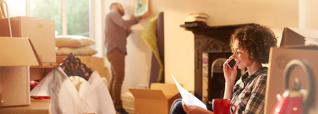 a couple move into their new home while woman talks on the phone whilst referring to a mortgage gift letter that she is holding