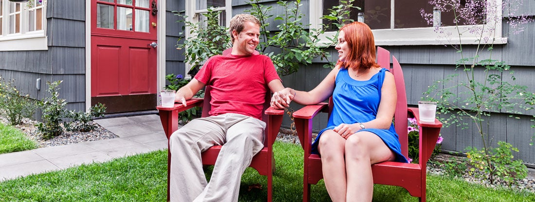 young couple in backyard discussing renting or buying home
