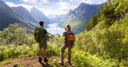 Two hikers at viewpoint in mountains with lake, sunny summer
