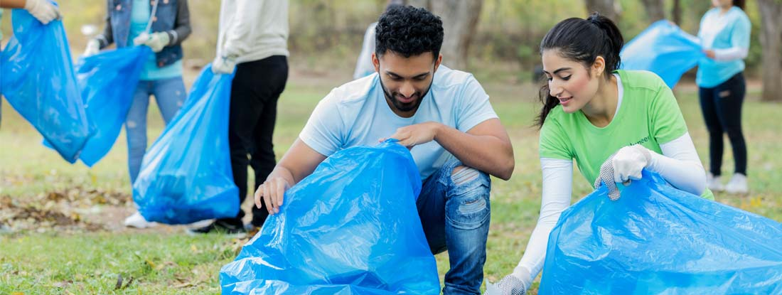 Young couple pick up litter together in public park