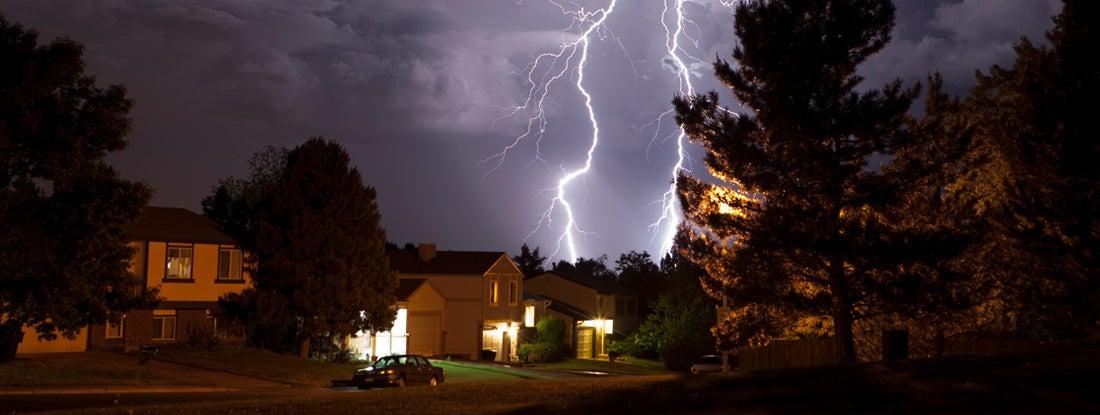 Lightning bolt and thunderhead storms over Denver neighborhood homes
