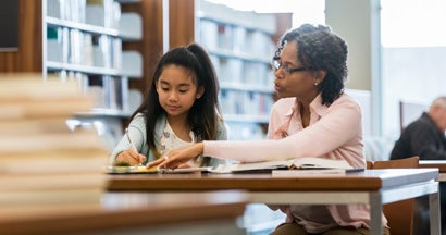 Tutor helps a female elementary school student study for a test.