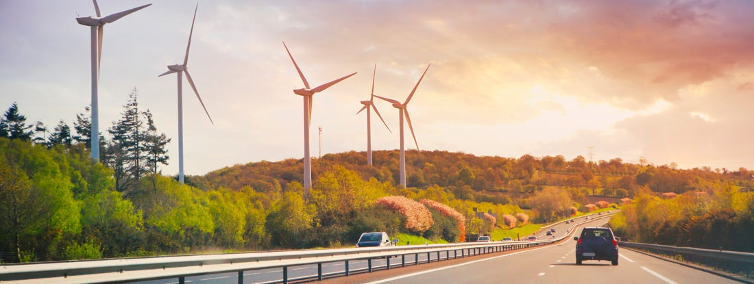 Cars going on highway in the landscape with wind propellers