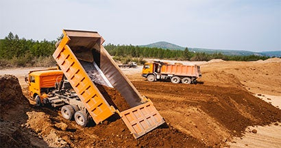 dump trucks delivering dirt to the construction site