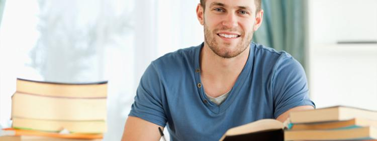 A smiling man at his desk at home, ready to take notes.