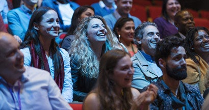 Smiling, enthusiastic audience in dark comedy club