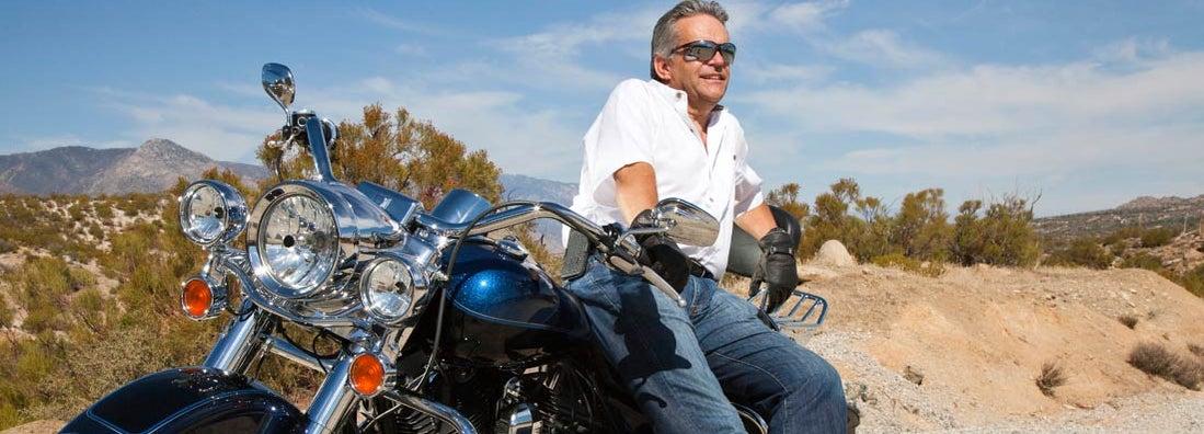 Senior man wearing sunglasses on motorcycle in desert. Find Arizona motorcycle insurance.
